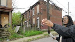 "Jerome Jackson of Operation Better Block standing in front of blighted properties owned by ""speculators"" in his neighborhood. Photo from the Post-Gazette."